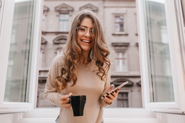 Blissful woman holding phone and laughing during photoshoot at home