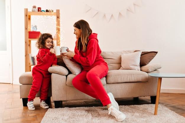 小さな娘とお茶を飲む赤い服装の至福の女性。ソファでポーズをとって笑顔の母と子の屋内ショット。