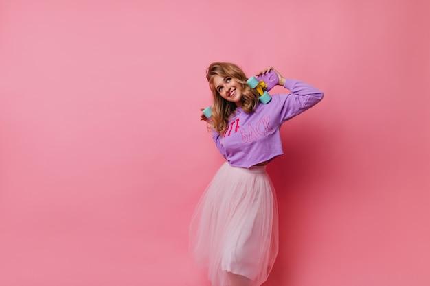 Beata donna in gonna lussureggiante sognante alzando lo sguardo. sorridente ragazza alla moda che tiene skateboard sul rosa.