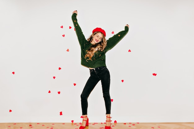 Blissful woman in red high heel shoes dancing on white wall under heart confetti