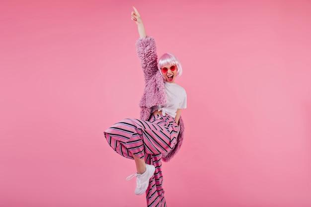 Блаженная женщина в полосатых штанах и розовом парике смеется во время фотосессии. уверенная барышня в солнечных очках и пушистой куртке, смешные танцы