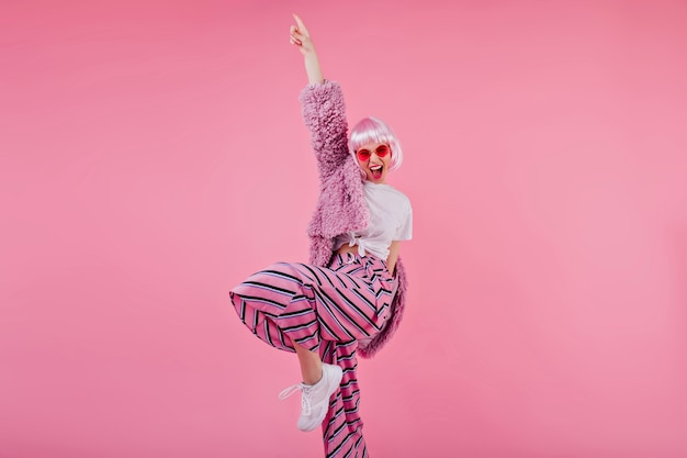 Blissful woman wears striped pants and pink periwig laughing during photoshoot. confident young lady in sunglasses and fluffy jacket funny dancing