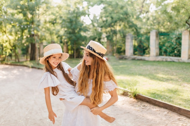 Blissful woman with long blonde hair carrying barefooted girl in trendy boater with nature. outdoor portrait of cheerful young mom spending time with kid in summer day.
