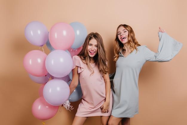 風船でポーズをとる短いピンクのドレスで至福の女性