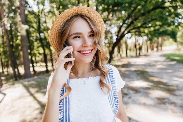 전화 대화 중에 웃 고 유행 밀 짚 모자에 행복 한 젊은 아가씨. 놀라운 백인 여자 전화 친구의 야외 사진.