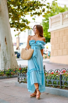 Blissful young lady walking alone at beautiful city european center, wearing elegant blue dress