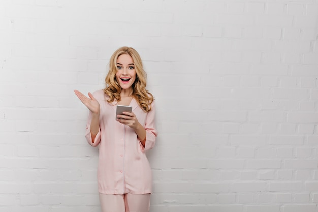 Blissful young woman in cotton sleepwear posing with phone in hands. indoor photo of charming blonde female model in pink pajamas isolated on white wall.