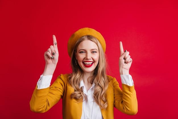 指で上向きのベレー帽の至福の若い女性。赤い壁に分離された素晴らしい笑顔の女の子の正面図。