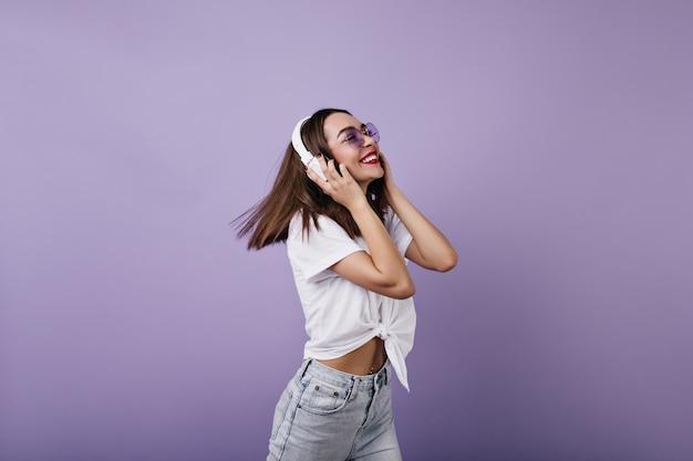 캐주얼 흰색 t- 셔츠 춤에서 행복 한 젊은 여자. 헤드폰으로 편안한 최신 유행의 옷에 황홀한 백인 여자.