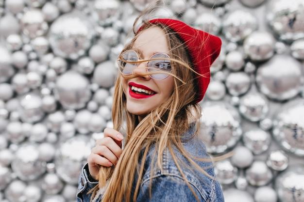 Beata giovane donna in posa davanti a palle da discoteca e ridendo. ritratto di romantica ragazza caucasica in cappello rosso alla moda e occhiali da sole.