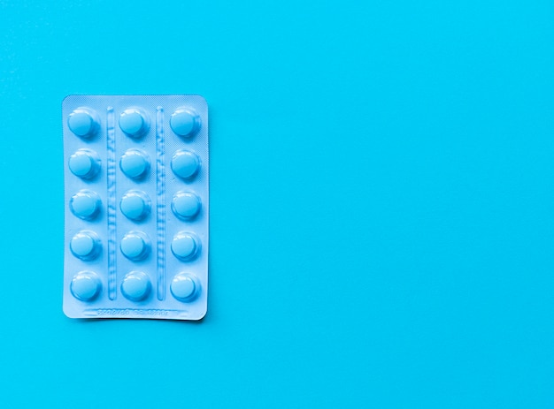 A blister of blue pills on blue background. monochrome simple flat lay with pastel texture with copy space. medical concept.