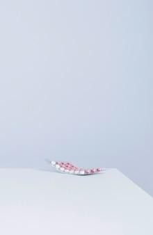 Блистерная упаковка с таблетками на краю стола на белом фоне