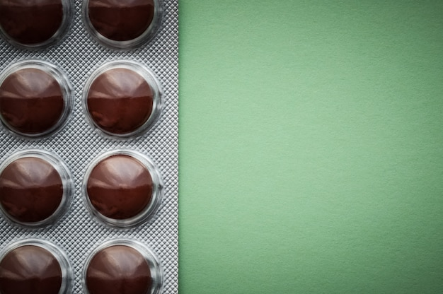 Blister with brown tablets on a green background.