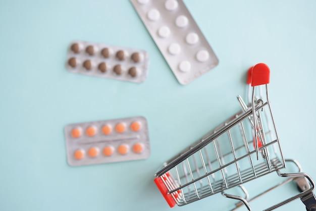 空のおもちゃの買い物かごのクローズアップの近くに横たわっている錠剤と水ぶくれ