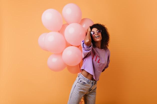 Allegra signora africana che balla all'evento. ragazza di buon compleanno in posa su arancia con un mazzo di palloncini.