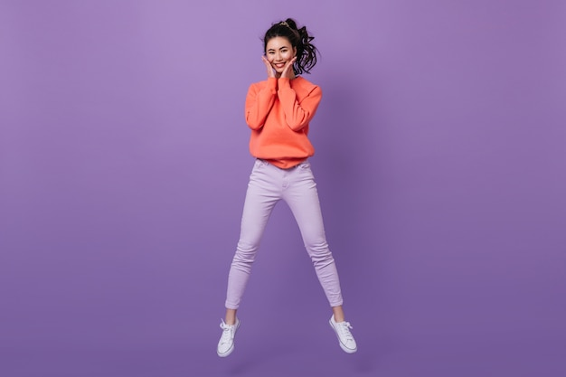 Blithesome 아시아 젊은 여자 점프 하 고 카메라를보고. 보라색 배경에 춤을 멋진 일본 여자.
