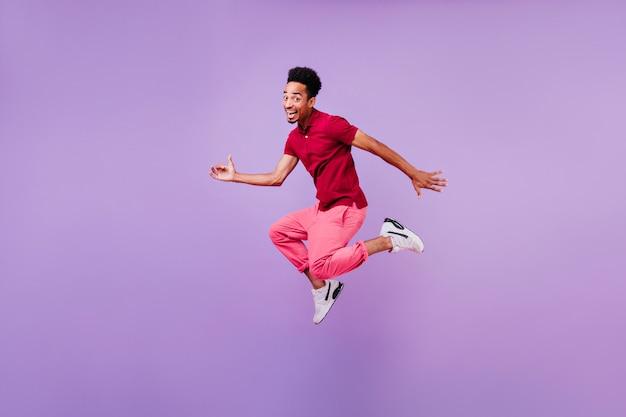 幸せな笑顔で踊る明るい黒のブルネットの男。赤いズボンと白い靴のジャンプでインスピレーションを得た男の屋内写真。