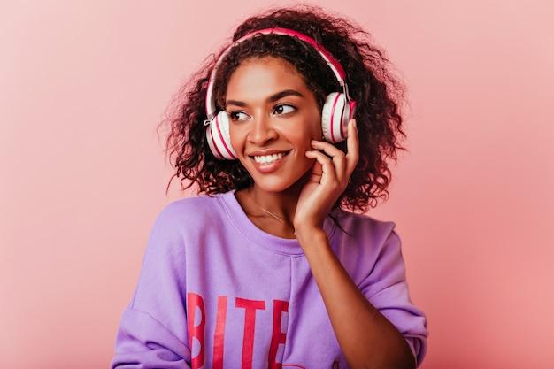 パステルで音楽を聴いている陽気な黒人の女の子。ヘッドフォンでポーズをとる紫色のセーターを着た魅力的なアフリカの女性。