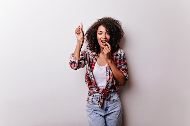 Веселая черная девушка с вьющейся прической, смешно позирует на белом. африканская красивая дама стоит с нежной улыбкой.