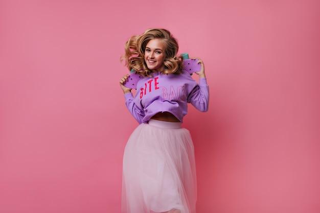 Беспечная блондинка в длинной юбке, держащей скейтборд. крытый портрет очаровательной женской модели с лонгбордом.
