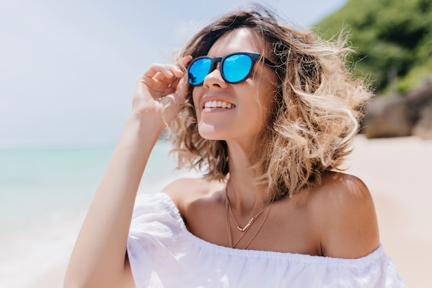 Blithesome blonde woman in sunglasses looking at sky. outdoor portrait of enchanting caucasian woman chilling at sandy beach.