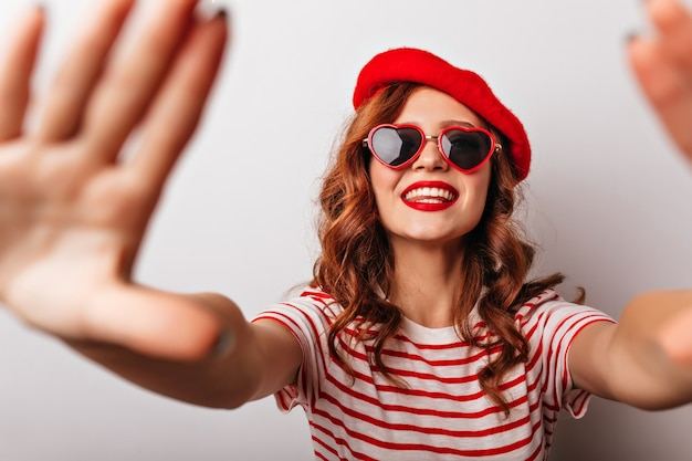 楽しんでいる赤いベレー帽の陽気な白人の女の子。サングラスでポーズをとる魅惑的な生姜女性モデル。