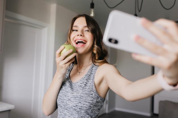 Ragazza caucasica allegra che cattura maschera di se stessa con la mela. ridendo amabile donna utilizza lo smartphone per selfie.