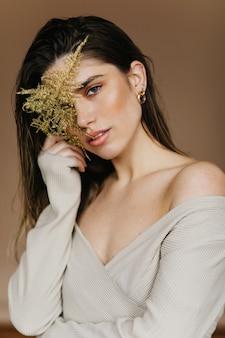 植物を保持している居心地の良い服装の明るい白人女性。緑の葉でポーズをとるロマンチックなブルネットの少女。
