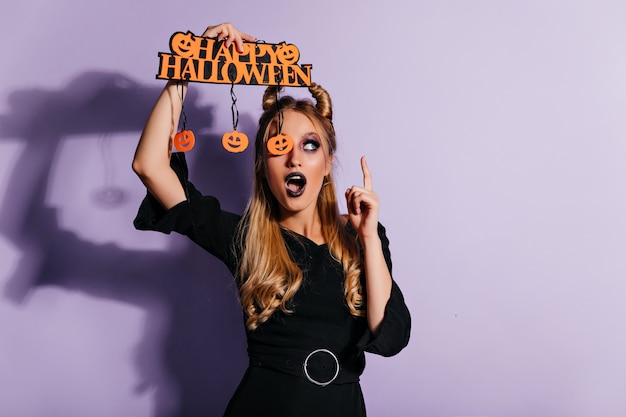 Blithesome caucasian woman in stylish black attire posing in halloween. charming witch standing on purple wall.