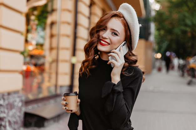 Allegra ragazza europea in berretto sorridente sul muro della città. affascinante signora dai capelli lunghi parlando al telefono e bevendo caffè.