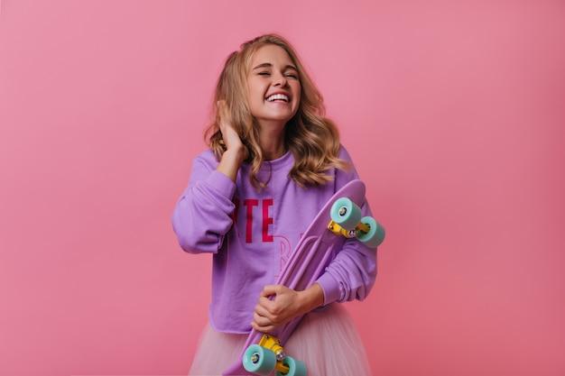 Веселая европейская девушка смеется над розовым. кудрявая женщина debonair, держащая фиолетовый скейтборд.