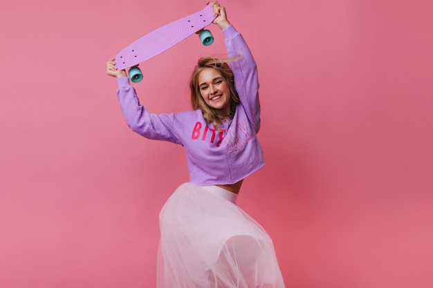 幸せそうな表情で踊る白いスカートの華やかな女性モデル。スケートボードとエレガントなブロンドの女の子の屋内の肖像画。