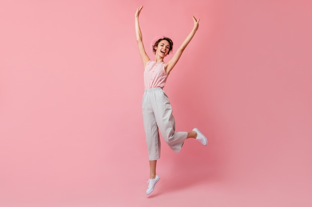 Blithesome french woman in pants jumping with hands up