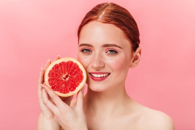 ジューシーなグレープフルーツを持っている陽気な生姜の女の子。ピンクの背景に幸せを表現するかなり若い女性。
