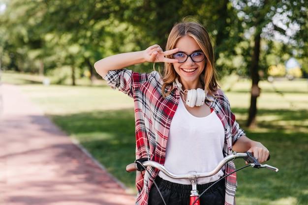 公園の周りに乗っている大きなヘッドフォンで明るい女の子。自然の中で自転車に座って笑っている愛らしい女性の屋外写真。