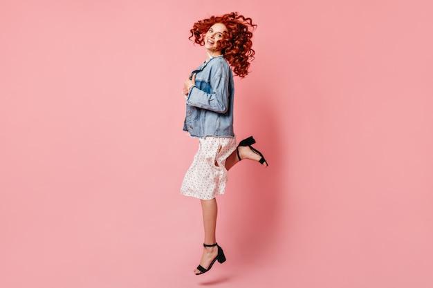 Беспечная девушка в платье танцует на розовом фоне. полнометражный вид возбужденной имбирной женщины в джинсовой куртке, прыгающей с улыбкой.