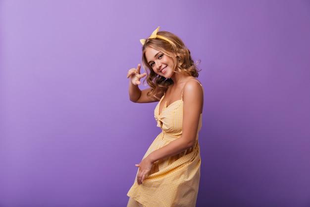 매력적인 미소로 춤추는 재미있는 청동 피부를 가진 blithesome 소녀. 노란색 옷에 화려한 백인 여자의 실내 초상화.