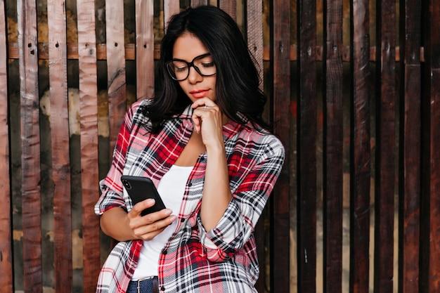 La ragazza allegra con i capelli lucidi legge il messaggio telefonico con interesse. ritratto all'aperto del modello femminile carino in bicchieri e camicia a scacchi.