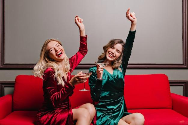 ベルベットの服を着た飲酒ワインの陽気な女の子。シャンパングラスとソファに座っている魅力的な女性の屋内の肖像画。