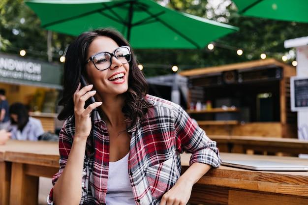 屋外のカフェに座って電話で話している陽気なラテン系の女の子。レストランで身も凍るようなメガネのきれいな女性フリーランサー。