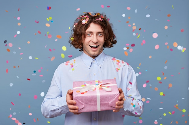 Blithesome long hair guy enjoying birthday with presents