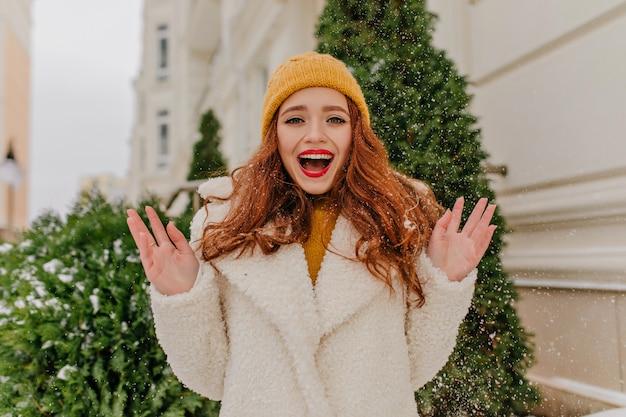 Donna dai capelli lunghi allegra che gode del fine settimana invernale. foto all'aperto della ragazza eccitata dello zenzero che scherza sulla strada.