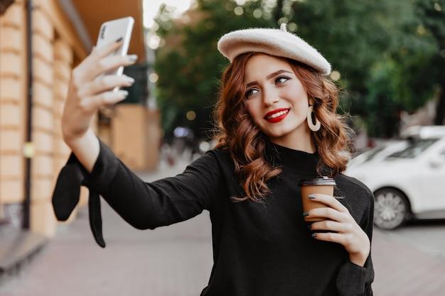 Ragazza dai capelli rossi allegra che tiene tazza di caffè e posa all'aperto. giovane signora francese spensierata che fa selfie sulla strada.