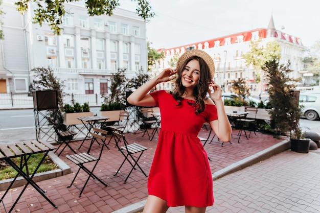 ストリートカフェの横でポーズをとっている陽気なスリムな女の子。街の写真撮影中に笑っている麦わら帽子で興奮した白人女性。