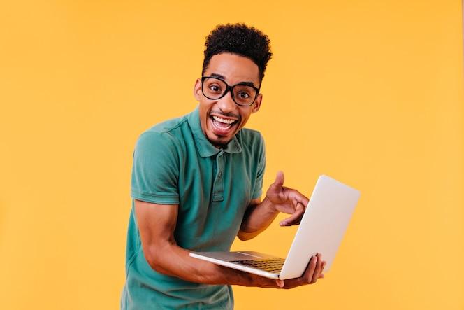 ノートパソコンでポーズをとる緑のtシャツを着た陽気な学生。孤立した驚いた男性フリーランサーの屋内写真。