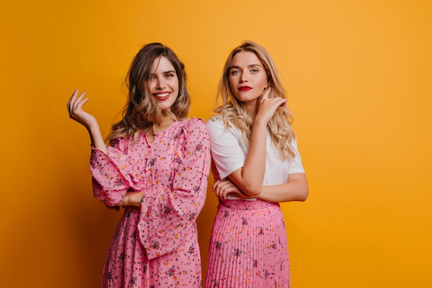 Blithesome white girl in dress relaxing with best friend. indoor shot of glad caucasian sisters isolated on yellow wall.
