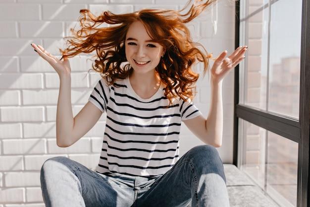 ウェーブのかかった髪で遊んでいる陽気な白人の女の子。生姜のんきな女性が笑っています。