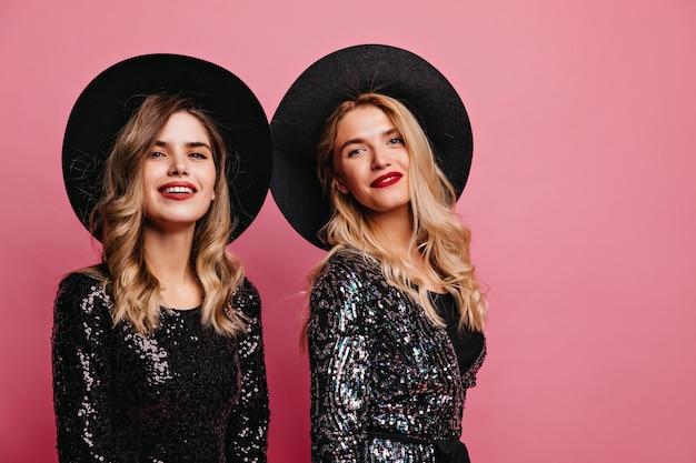 Donne bianche allegre in cappelli che posano sul muro roseo. ritratto dell'interno di ragazze caucasiche fiduciose con accessori glamour.