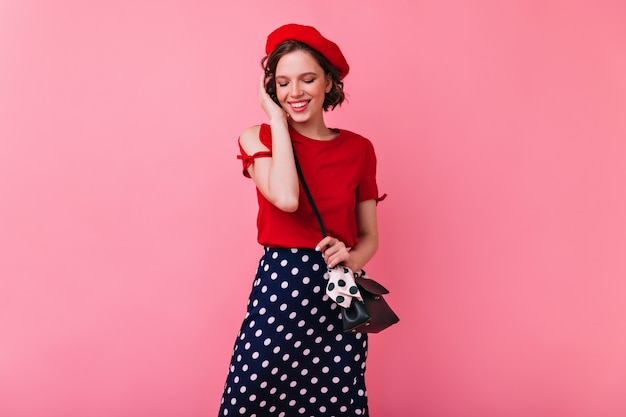 Donna bianca allegra in camicetta rossa che osserva giù con il sorriso. foto interna della timida ragazza francese in berretto.