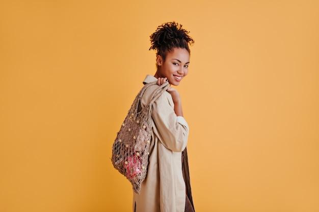 正面を見てストリングバッグを持った快活な女性
